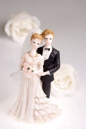 Figurines of wedding couple on light background with roses. photo