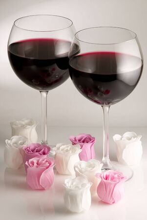 Two glasses of red wine and roses on light background. photo