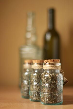 Jars of spices and vintage bottles on brown wood surface. Stock Photo - 4239815