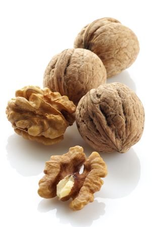 Walnut: Whole and hulled walnuts on white background.