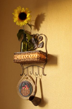 Kitchen wicker shelf with sunflower and kitchenware. photo