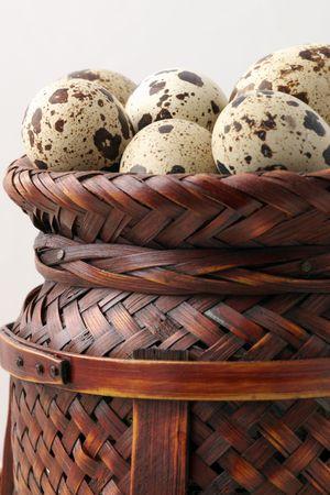 speckle: Quail eggs in wicker basket on beige background.