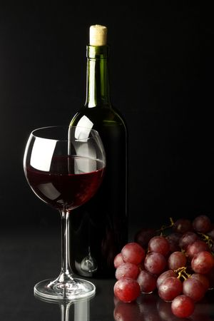 Glass of red wine, bottle and bunch of grape on black background. Stock Photo - 4417904