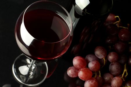 Glass of red wine, bottle and bunch of grape on black background. photo