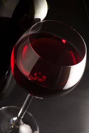 Glass of red wine and bottle close-up on black background. Stock Photo - 4454356