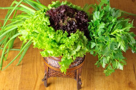Bunch of lettuce, spring onion and parsley in wicker basket on wood surface. photo