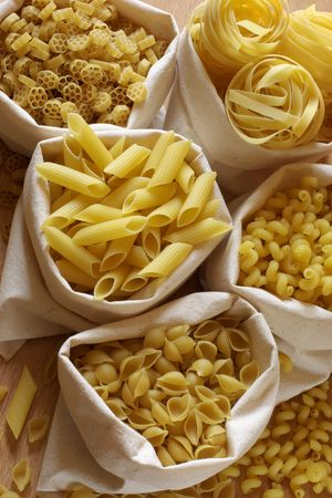 Various raw shaped pasta in textile bags. Stock Photo