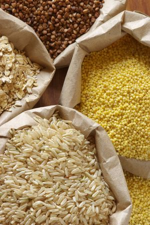Brown rice, oatmeal, millet and buckwheat in paper bags. Stock Photo - 4869771