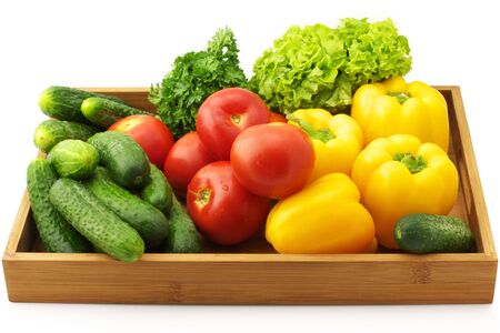 Yellow pepper, tomatoes, cucumbers, lettuce and parsley in wooden tray. photo