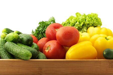 Yellow pepers, tomatoes, cucumbers, lettuce and parsley in wooden tray. photo