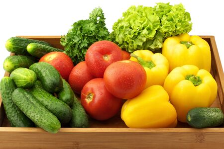 Yellow peppers, tomatoes, cucumbers, lettuce and parsley in wooden tray. photo