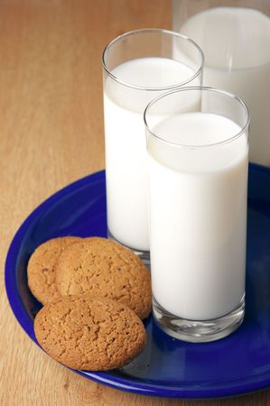 Bottle, two glasses of milk and oat cookies on blue plate. photo