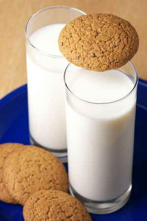 Two glasses of milk and oat cookies on blue plate. photo