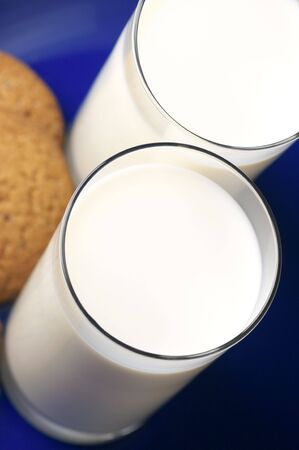 Two glasses of milk close-up and oat cookies on blue plate. photo