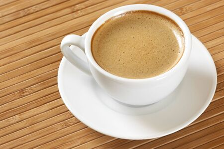 spume: White cup of coffee with saucer on wooden mat.