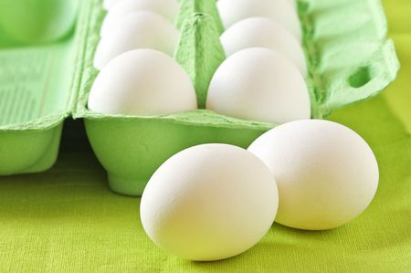 White chicken eggs in green carton box on lime color background. photo