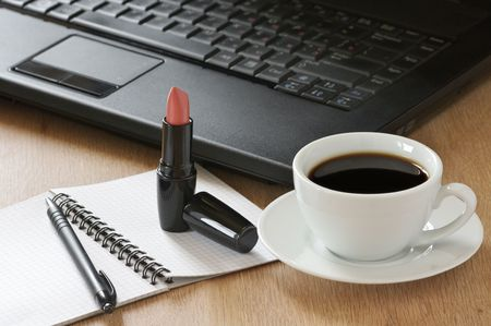 Laptop, notepad, pen, lipstick and cup of coffee on wooden desk. photo