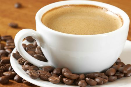 spume: White cup of coffee and coffee beans on wooden surface.