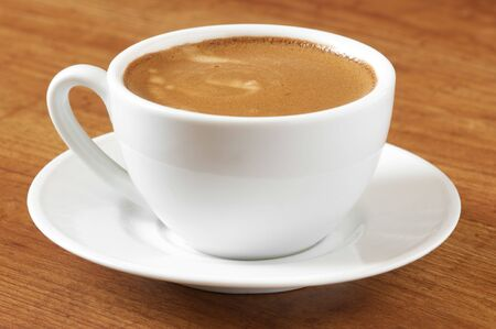 spume: White cup of coffee with saucer on wooden surface.