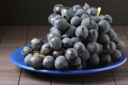 patina: Bunch of fresh ripe dark grape with patina on blue plate. Stock Photo