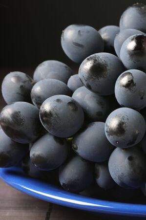 patina: Bunch of fresh ripe dark grape with patina and dust close-up.