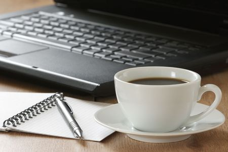 Laptop, notepad, pen and cup of coffee on wooden desk. Stock Photo