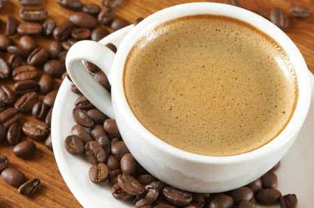White cup of coffee with saucer and coffee beans on wooden surface. Stock Photo - 5612067