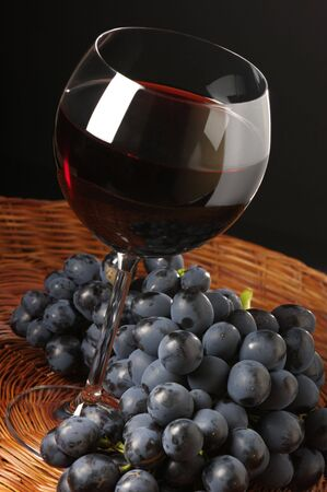 Glass of red wine and bunch of black grape on wicker tray. Stock Photo - 5612052