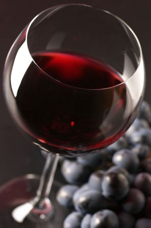 Glass of red wine and bunch of black grape close-up on dark background. Selective focus on front edge of glass.