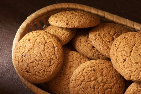 Heap of oatmeal cookies in wicker bowl on brown canvas. photo