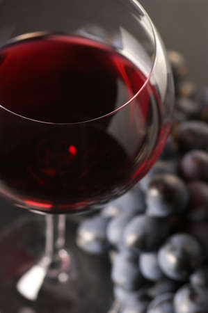 Glass of red wine and bunch of black grape close-up on dark background. Selective focus on front edge of glass. Reklamní fotografie