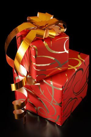 Two ornamented red gifts with gold bow on black background. photo