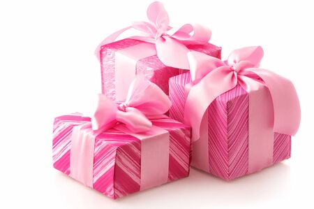 three presents: Three pink gifts with satin bows isolated on white background.