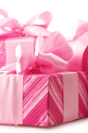 Three pink gifts with satin bows close-up on white background. photo