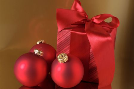 Red Christmas decorations and red gift on gold background. photo