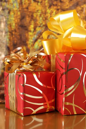 Two red and gold gifts on gold sparkling background. photo