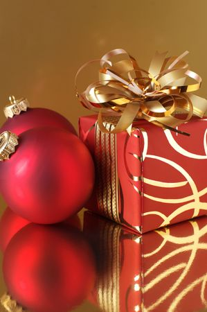 Red Christmas decorations and redgold gift on gold background.