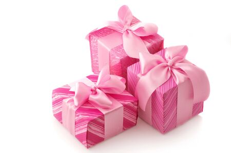 Three pink gifts with satin bows isolated on white background. photo
