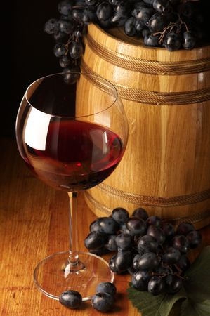 Glass of red wine, dark grape and souvenir barrel on wooden surface. Stock Photo - 5979426