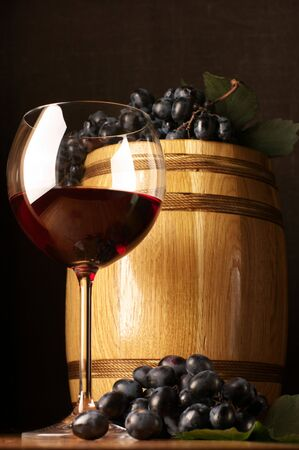 Glass of red wine, dark grape and souvenir barrel on wooden surface. Stock Photo - 6076151
