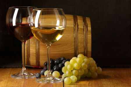 Glasses of red and white wine, grape and souvenir barrel on wooden surface. photo