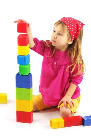 preschooler: Nice little girl playing with colorful bricks on white background. Stock Photo