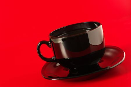 Black glass cup of coffee with saucer on red background. photo