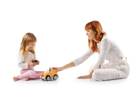 adult offspring: Playing mother and daughter in white sitting on white background. Stock Photo