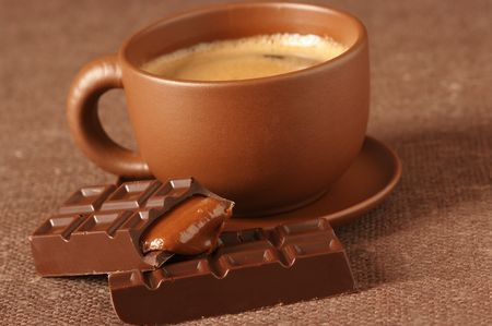 Brown ceramic cup of coffee with froth and broken chocolate bar with caramel stuffing on brown canvas. photo