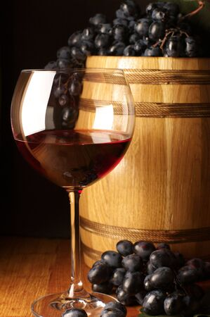 Glass of red wine, dark grape and souvenir barrel on wooden surface. Stock Photo - 6209905