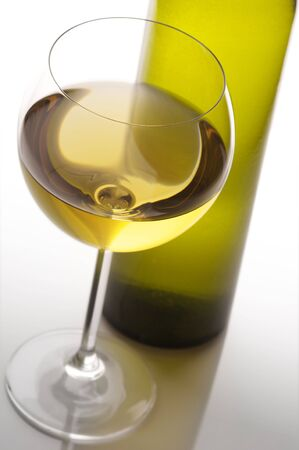 white wine: Close-up of glass of white wine and bottle in back light on light background.