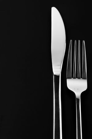 silver flatware: Stainless knife and fork on black background with copy space. Stock Photo
