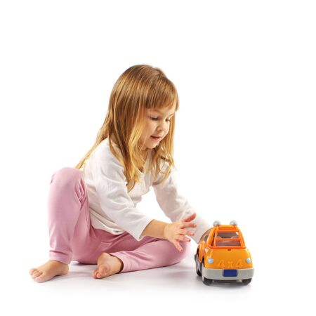 little girl sitting: Nice little girl playing with toy car on white background. Stock Photo