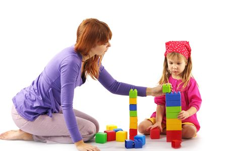 Mother and daughter playing with colorful bricks on white background. photo